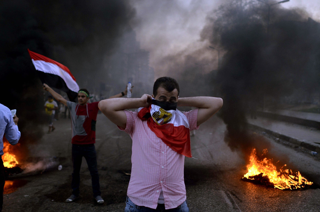 . An Egyptian protestor covers his face with his national flag during clashes between supporters of the Muslim Brotherhood and Egypt\'s ousted president Mohamed Morsi and security forces, in Cairo, on August 30, 2013. Several thousand Egyptians protested in Cairo in support of ousted president Mohamed Morsi, their turnout far lower than hoped for by the harried Islamists who called for mass rallies. MOHAMED EL-SHAHED/AFP/Getty Images