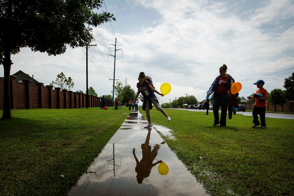 . Plaza Towers elementary school student Kayla Billy leans over a puddle in front of her mother Jennifer Billy (C) and brother Ethan Billy (R) as she departs a ceremonial last day of the school year at the Eastlake Elementary School in Moore, Oklahoma, May 23, 2013. Seven students were killed at Plaza Towers Elementary when a tornado packing winds of 200 miles (320 km) per hour slammed into the building on Monday afternoon just before school was to have let out. The massive tornado obliterated sections of Moore, Oklahoma, leaving 24 dead on May 20. REUTERS/Lucas Jackson