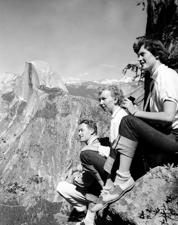 . Three hikers pause to rest near firefall ledge on the ledge climb to Glacier Point from Yosemite Valley in Yosemite National Park in California, July 8, 1952. In background is famed Half Dome, chief landmark of the Valley. Left to right: Reed Campbell, of Taft, Calif.; Robin Yelland, of Berkley, Calif., and her cousin, Gwen Yelland, of Clarksburg, Calif. (AP Photo/Ernest K. Bennett)
