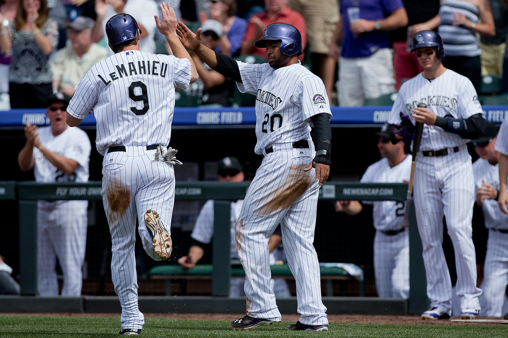 . DJ LeMahieu #9 of the Colorado Rockies celebrates with Wilin Rosario #20 after scoring during the third inning against the San Diego Padres at Coors Field on May 18, 2014 in Denver, Colorado. The Rockies defeated the Padres 8-6 in 10 innings. (Photo by Justin Edmonds/Getty Images)