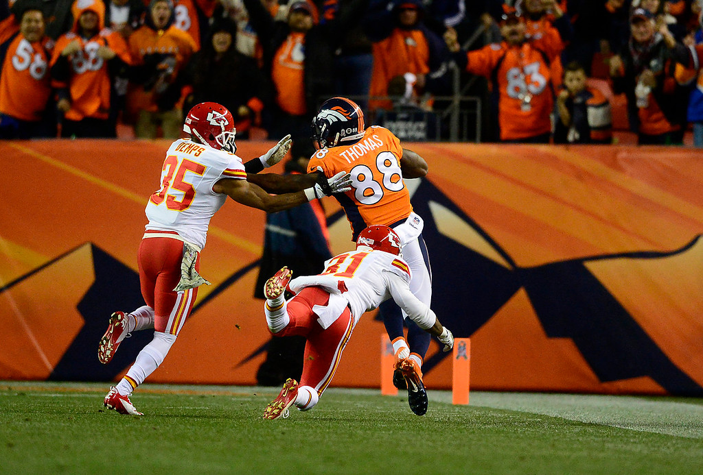 . Denver Broncos wide receiver Demaryius Thomas (88) is pushed out of bounds by Kansas City Chiefs defensive back Quintin Demps (35) and Kansas City Chiefs cornerback Marcus Cooper (31) after a 70-yard gain in the first quarter. The Denver Broncos take on the Kansas City Chiefs at Sports Authority Field at Mile High in Denver on November 17, 2013. (Photo by AAron Ontiveroz/The Denver Post)