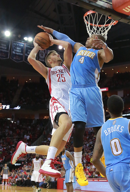 . Houston Rockets forward Chandler Parsons goes up for a shot against Denver Nuggets guard Randy Foye during overtime of an NBA basketball game in Houston on Sunday, April 6, 2014. The Rockets won 130-125.  (AP Photo/Richard Carson)