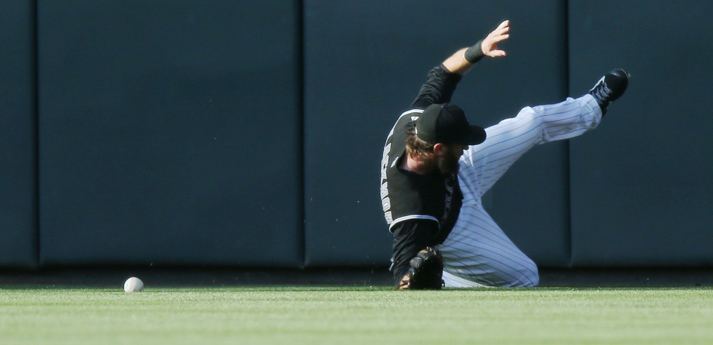 . Colorado Rockies centerfielder Charlie Blackmon runs into the wall while tryng to chase down a triple off the bat of Chicago Cubs leadoff hitter Chris Coghlan in the first inning of a baseball game in Denver on Wednesday, Aug. 6, 2014. (AP Photo/David Zalubowski)