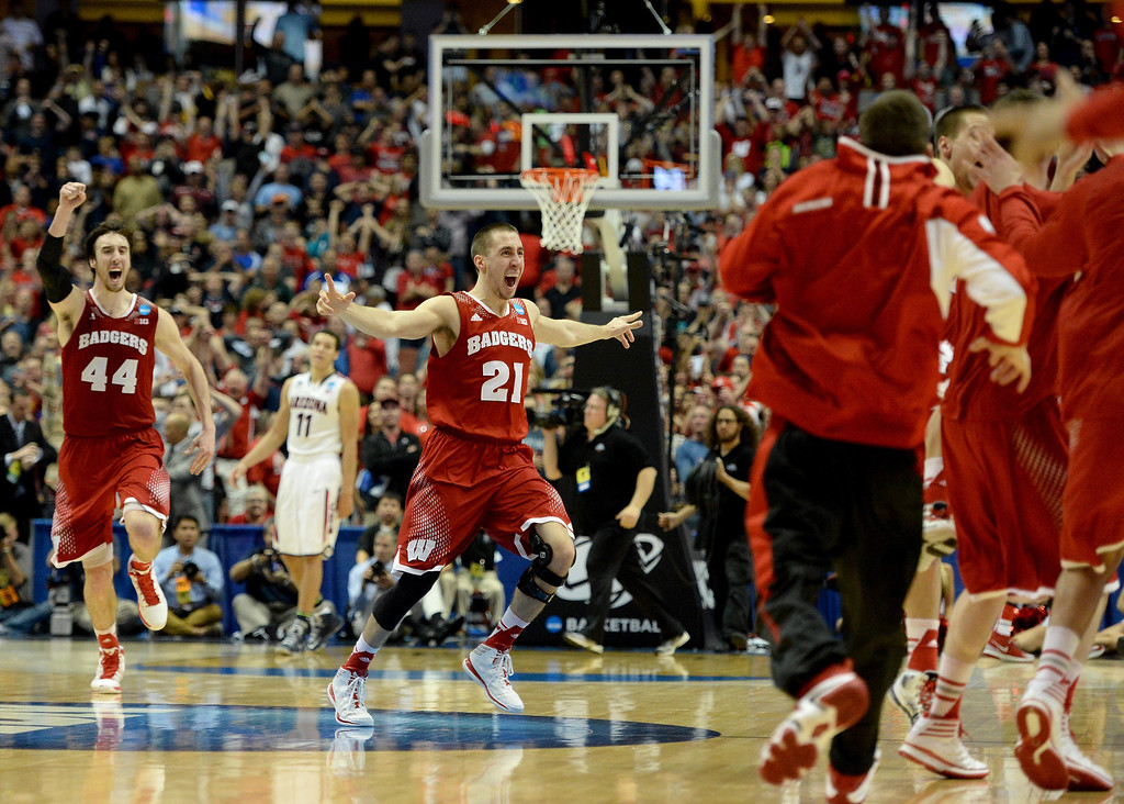 . Josh Gasser #21 and Frank Kaminsky #44 of the Wisconsin Badgers celebrate after defeating the Arizona Wildcats 64-63 in overtime during the West Regional Final of the 2014 NCAA Men\'s Basketball Tournament at the Honda Center on March 29, 2014 in Anaheim, California.  (Photo by Harry How/Getty Images)