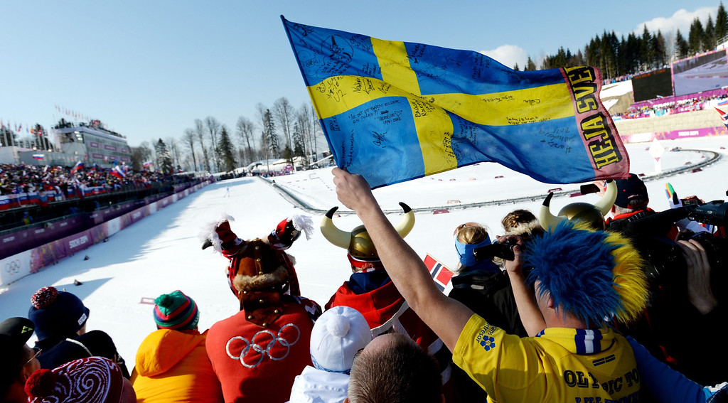 . A Swedish fan waves his country\'s flag as Sweden\'s Marcus Hellner crosses the finish line to win the Men\'s 4 X 10km Relay competition at the Laura Cross Country Center during the Sochi 2014 Olympic Games, Krasnaya Polyana, Russia, 16 February 2014.  EPA/JUSTIN LANE