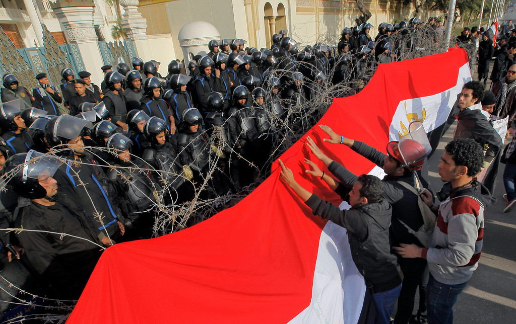 . Egyptian protesters hang a giant banner in the colors of Egypt\'s national flag on barbed wires in front of anti-riot soldiers at the entrance to the presidential palace in Cairo, Egypt, Friday, Jan. 25, 2013. Two years after Egypt\'s revolution began, the country\'s schism was on display Friday as the mainly liberal and secular opposition held rallies saying the goals of the pro-democracy uprising have not been met and denouncing Islamist President Mohammed Morsi. (AP Photo/Amr Nabil)