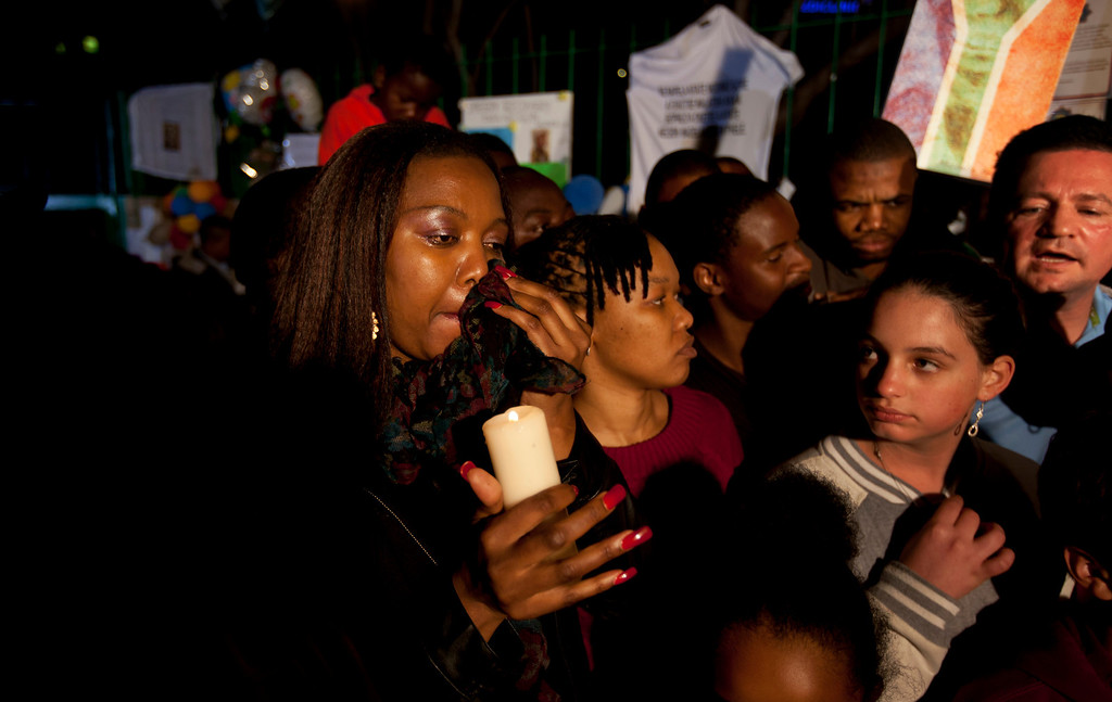 . A woman from a community group from Pretoria sheds a tear as she holds a candle, as she and others show their appreciation and support for former South African President Nelson Mandela, on the street outside the Mediclinic Heart Hospital where he is being treated in Pretoria, South Africa Tuesday, June 25, 2013. South Africa\'s president Jacob Zuma on Tuesday urged his compatriots to show their appreciation for Nelson Mandela, who is in critical condition in a hospital, by marking his 95th birthday next month with acts of goodness that honor the legacy of the anti-apartheid leader. (AP Photo/Ben Curtis)