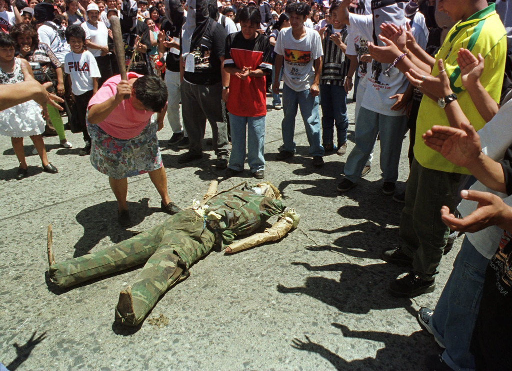 ". An unidentified woman beats an effigy of former military leader Efrain Rios Montt during the 101st annual Huelga de Dolores in Guatemala City Friday, March 26, 1999. The annual march is a method in which the university students let their grievances with the Guatemalan government be known. Rios Montt was a general who seized power in a March 1982 coup and governed until he was overthrown in August 1983.  During his rule, the army burned Indian villages and killed thousands of suspected leftists.  While beating the effigy, other students shouted, ""First Pinochet, now Rios Montt,\"" in a cry for the former military leader to be tried for his crimes. (AP Photo/Scott Dalton)"