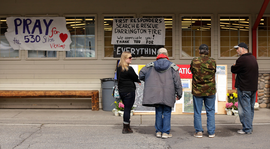 ". Shoppers pause at an information board in front of the Darrington IGA, next to a sign that reads ""Pray for the 530 slide victims,\"" at the main grocery store in town, Thursday, March 27, 2014, in Darrington, Wash. (AP Photo/Ted S. Warren)"