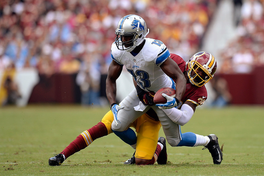 . Nate Burleson #13 of the Detroit Lions is tackled by David Amerson #39 of the Washington Redskins after catching a pass from Matthew Stafford #9 (not pictured) in the first quarter during a game at FedExField on September 22, 2013 in Landover, Maryland.  (Photo by Patrick McDermott/Getty Images)