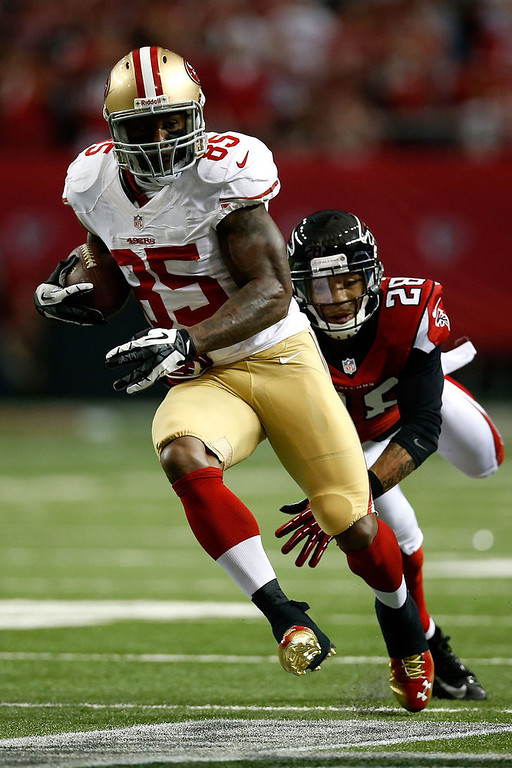 . Tight end Vernon Davis #85 of the San Francisco 49ers runs after a catch in front of free safety Thomas DeCoud #28 of the Atlanta Falcons in the second quarter in the NFC Championship game at the Georgia Dome on January 20, 2013 in Atlanta, Georgia.  (Photo by Chris Graythen/Getty Images)