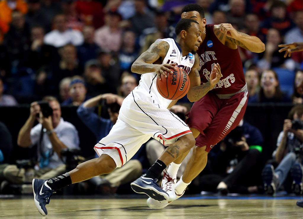 . BUFFALO, NY - MARCH 20: Ryan Boatright #11 of the Connecticut Huskies drives to the basket as Chris Wilson #24 of the Saint Joseph\'s Hawks defends during the second round of the 2014 NCAA Men\'s Basketball Tournament at the First Niagara Center on March 20, 2014 in Buffalo, New York.  (Photo by Elsa/Getty Images)