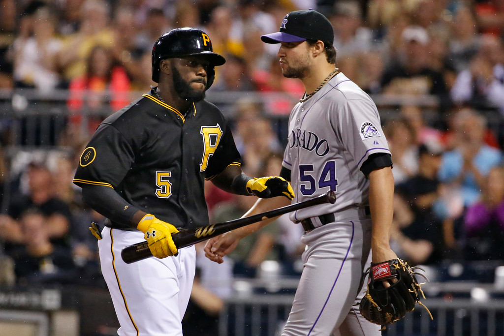 . Pittsburgh Pirates\' Josh Harrison (5) carries his bat back to the dugout past Colorado Rockies relief pitcher Tommy Kahnle (54) after driving in a run with a sacrifice fly in the eighth inning of a baseball game in Pittsburgh on Friday, July 18, 2014. The Pirates won 4-2. (AP Photo/Gene J. Puskar)