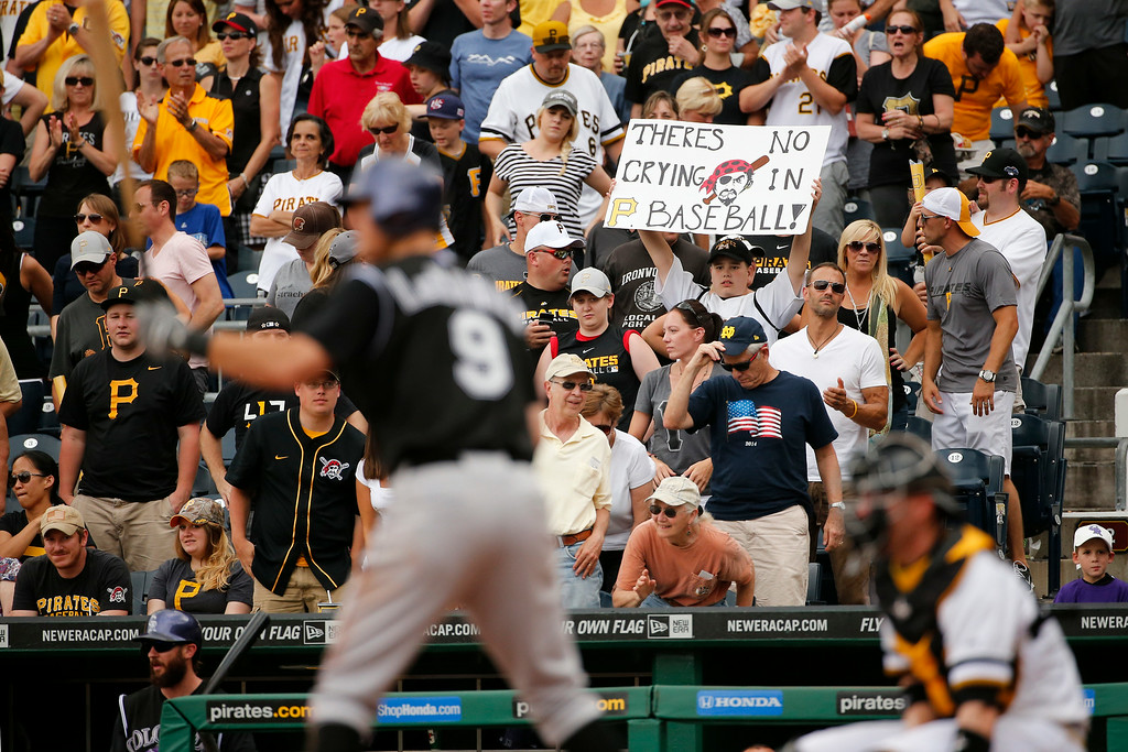 . A Pittsburgh Pirates fan holds a sign as Colorado Rockies\' DJ LeMahieu (9) bats in the ninth inning of a baseball game against the Pittsburgh Pirates in Pittsburgh Sunday, July 20, 2014. LeMahieu struck out swinging to end the game. The Pirates won 5-3. (AP Photo/Gene J. Puskar)