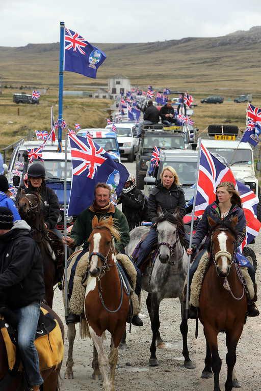 """. Islanders take part in the \""""Proud to be British\"""" parade along Ross Road in Port Stanley, Falkland (Malvinas for Argentina) Islands, on March 10, 2013.  Falkland Islanders were to vote Monday on the final day of a two-day referendum designed to make clear their staunch desire to remain British despite Argentina\'s increasingly bellicose sovereignty claims. TONY CHATER/AFP/Getty Images"""