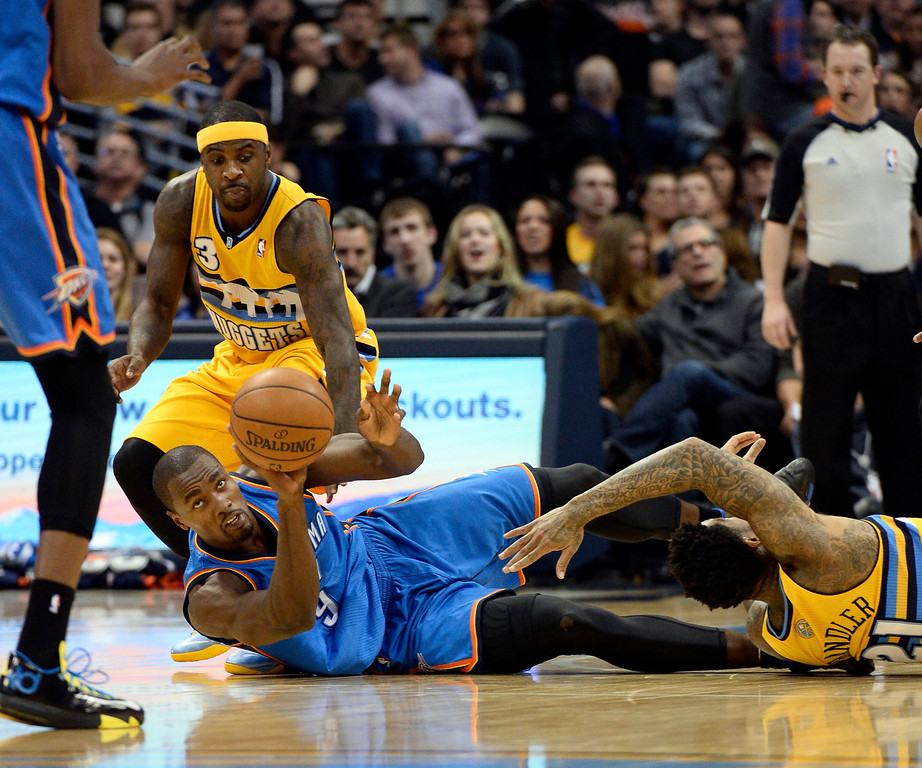 . Oklahoma City Thunder forward Serge Ibaka attempts to keep control of the ball on the floor during the second quarter Tuesday night at the Pepsi Center as Nuggets guard Ty Lawson (3) and Wilson Chandler (21) tries to take it away on Tuesday, Dec. 17, 2013. (Photo by John Leyba/The Denver Post)