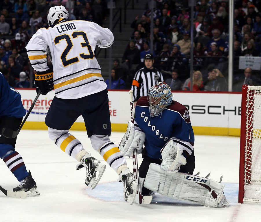. Buffalo Sabres left wing Ville Leino (23), left, of Finland, jumps to avoid a shot as Colorado Avalanche goalie Semyon Varlamov covers the net in the third period of the Avalanche\'s 7-1 victory in an NHL hockey game in Denver, Saturday, Feb. 1, 2014. (AP Photo/David Zalubowski)