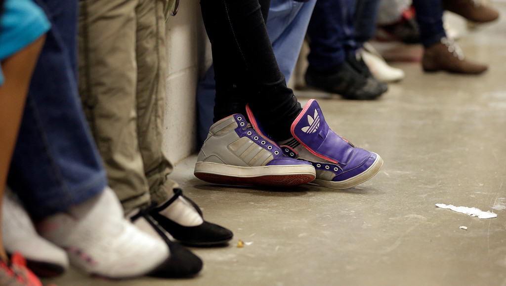 . Detainees, with the shoe strings removed, wait at a U.S. Customs and Border Protection processing facility, Wednesday, June 18, 2014, in Brownsville,Texas.  (AP Photo/Eric Gay, Pool)