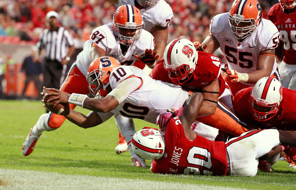 . Syracuse quarterback Terrel Hunt (10) scores on a eight-yard touchdown during the fourth quarter of an NCAA college football game against North Carolina State on Saturday, Oct. 12, 2013, at Carter-Finley Stadium in Raleigh, N.C. (AP Photo/The News & Observer,  Ethan Hyman)