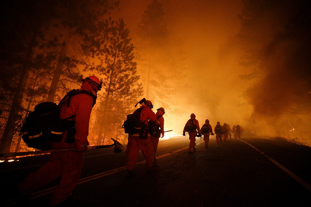 . Inmate firefighters walk along Highway 120 after a burnout operation as firefighters continue to battle the Rim Fire near Yosemite National Park, Calif., on Sunday, Aug. 25, 2013.  (AP Photo/Jae C. Hong)