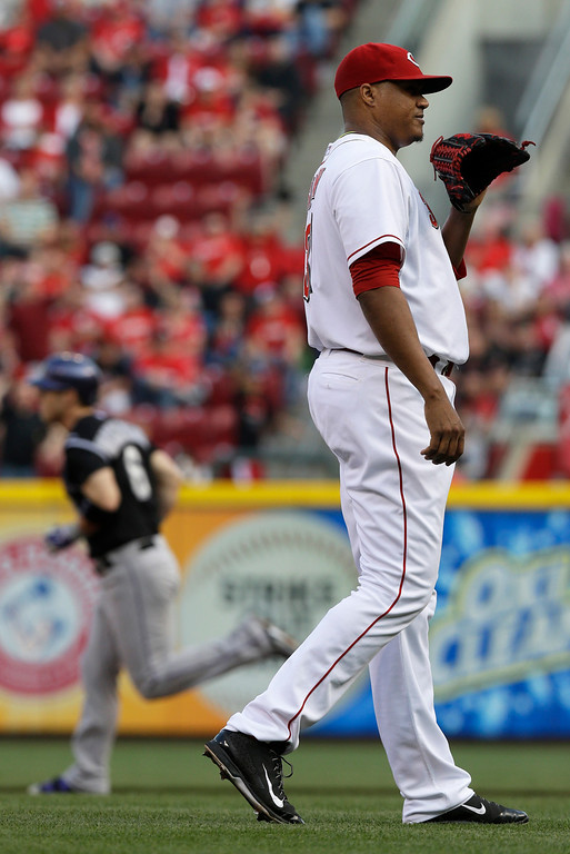 . Cincinnati Reds starting pitcher Alfredo Simon, right, stands on the mound after giving up a home run to Colorado Rockies\' Corey Dickerson (6) in the first inning of a baseball game on Saturday, May 10, 2014, in Cincinnati. (AP Photo/Al Behrman)
