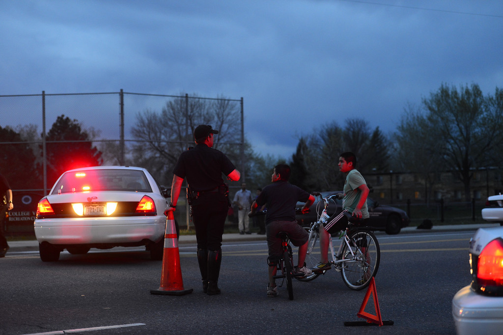 . DENVER, CO - MAY 14: Traffic officer Luke Palmatier speaks with neighborhood children Luis Martinez, 13, and David Torres, 11, as police investigate the scene of an officer-involved shooting near the intersection of Harvard and Federal Boulevard. (Photo by AAron Ontiveroz/The Denver Post)