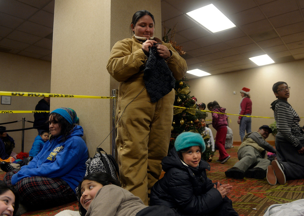 . Olga Reyes, center, knits as she waits for the Father Woody Christmas Party to begin on Dec. 22 at the Sheraton Denver Downtown Hotel in Denver, Colo. Around 5,000 people attended the annual event, where a warm meal was served, gifts were handed out, and children could visit with Santa. Photo By Jamie Cotten, Special to The Denver Post