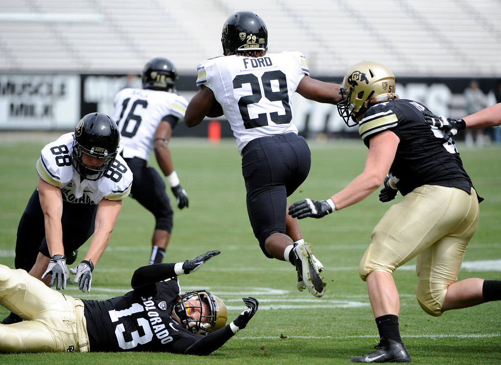 . BOULDER, CO.- APRIL13: Josh Ford leaps over Parker Orms as he move down field. The University of Colorado football team hosts its spring football game at Folsom Field under the direction of new head coach Mike MacIntyre. (Photo By Kathryn Scott Osler/The Denver Post)
