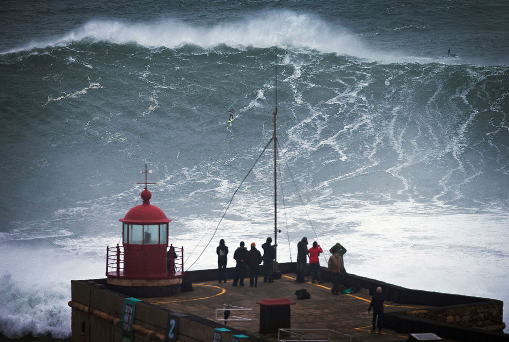 . People watch an unidentified surfer ride a big wave at the Praia do Norte, north beach, at the fishing village of Nazare in Portugal\'s Atlantic coast Monday, Oct. 28 2013. On Monday Brazilian suffer Carlos Burle surfed a wave here that surf media suggest could be the biggest wave ever surfed and Maya Gabeira, also from Brazil, nearly drowned and was taken to hospital with a broken ankle after falling in a big wave. (AP Photo/Miguel Barreira)