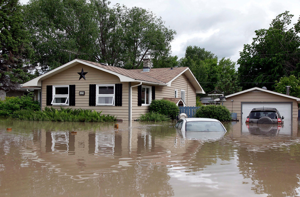 . Cars and homes are submerged in flood waters in High River, Alberta, Thursday, June 20, 2013. Calgary city officials say as many as 100,000 people could be forced from their homes due to heavy flooding in western Canada, while mudslides have forced the closure of the Trans-Canada Highway around the mountain resort towns of Banff and Canmore.