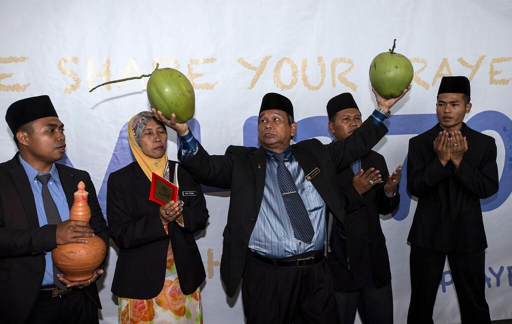 . Malaysian shaman, Ibrahim Mat Zin (3-L) performs a ritual that he claims can locate the missing Malaysian Airlines MH370 at Kuala Lumpur International Airport, Sepang, Selangor, Malaysia, 12 March 2014.  EPA/AHMAD YUSNI