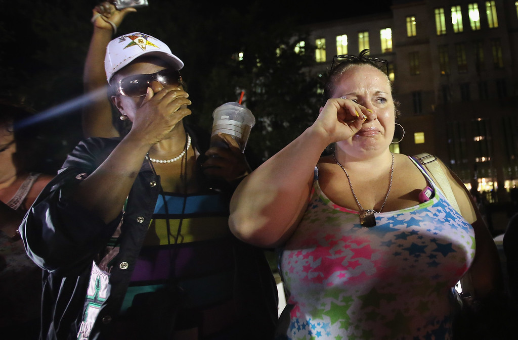 . SANFORD, FL - JULY 13:  Kat Crowe (L) and Melinda O\'Neal react in front of the Seminole County Criminal Justice Center after learning George Zimmerman had been found not guilty in the Murder of Trayvon Martin on July 13, 2013 in Sanford, Florida. Zimmerman, a neighborhood watch volunteer, shot and killed 17-year-old Martin after an altercation in February 2012.  (Photo by Scott Olson/Getty Images)