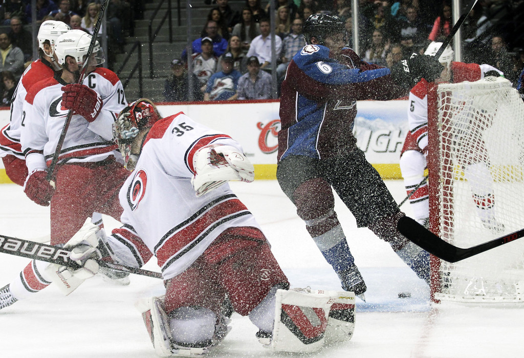 . Colorado Avalanche defenseman Erik Johnson (6) collides with the goal after scoring against Carolina Hurricanes goalie Justin Peters (35) and Hurricanes center Eric Staal (12) in the first period of an NHL hockey game in Denver on Friday, Oct. 25, 2013.(AP Photo/Joe Mahoney)