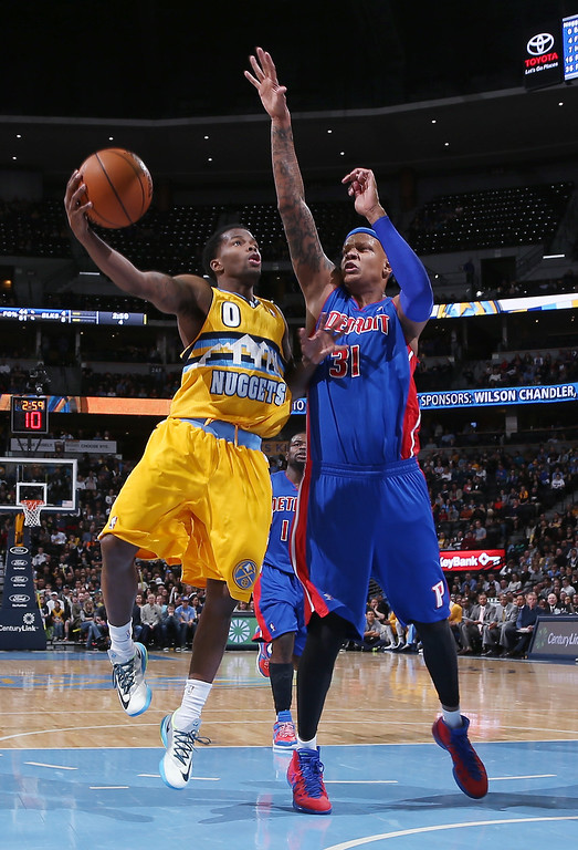. Denver Nuggets guard Aaron Brooks, left, drives for shot as Detroit Pistons forward Charlie Villanueva covers in the fourth quarter of the Nuggets\' 118-109 victory in an NBA basketball game in Denver on Wednesday, March 19, 2014. (AP Photo/David Zalubowski)