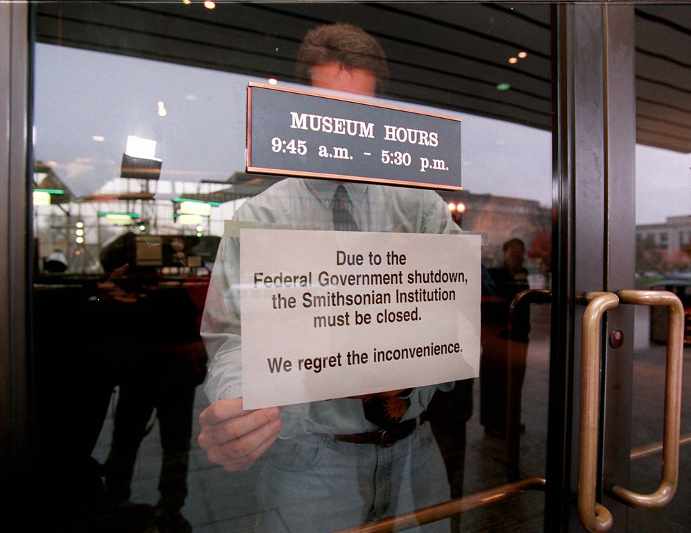 . Mike Fetters afixes a closed sign on a door at the Smithsonian\'s Air and Space Museum in Washington Tuesday Nov. 14, 1995 as parts of the federal government were shutdown due a federal budget impasse between President Clinton and the Republican Congress. Moments later, the sign was taken down and the museum opened as all Smithsonian museums in Washington were told from their headquarters to stay open until further notice. (AP Photo/Doug Mills)