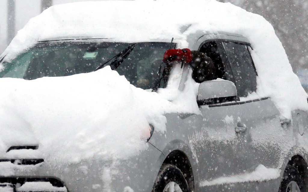 . A commuter stops his car on the snowy road as he checks his wiper blades in Chicago, Thursday, Jan. 2, 2014. Another one to three inches of snow could fall across the Chicago metro area Thursday with even more falling in the southern part of the region, according to the National Weather Service. (AP Photo/Nam Y. Huh)