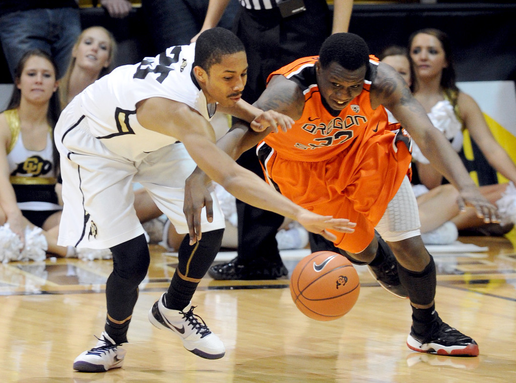 . Spencer Dinwiidie, left, of Colorado, and Jarmal Reid of Oregon State go to the floor after a loose ball during the first half of the March 9, 2013 game in Boulder.    (Cliff Grassmick/Boulder Daily Camera)