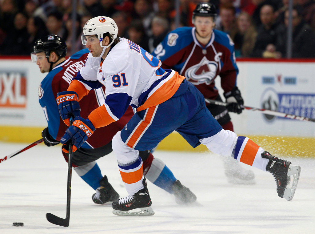 . New York Islanders center John Tavares, front, picks up loose puck next to Colorado Avalanche center John Mitchell as left wing Gabriel Landeskog, back, of Sweden, watches during the first period of an NHL hockey game in Denver on Friday, Jan. 10, 2014. (AP Photo/David Zalubowski)