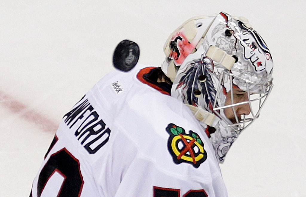 . A puck goes past the shoulder of Chicago Blackhawks goalie Corey Crawford (50) during the second period in Game 6 of the NHL hockey Stanley Cup Finals, Monday, June 24, 2013, in Boston. (AP Photo/Charles Krupa)