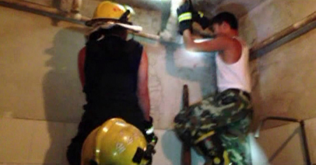 . In this still image taken from video from Saturday May 25, 2013, a firefighter attempts to remove a section of a sewage pipe where a newborn baby appears trapped, in Pujiang in east China\'s Zhejiang province. (AP Photo)