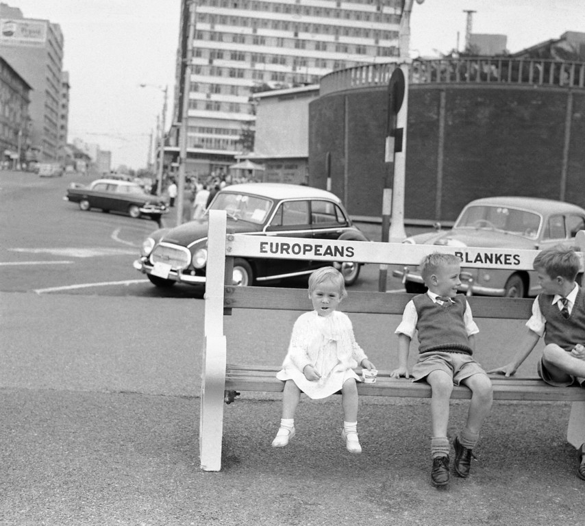 . Children sit on bench along waterfront in Durban, a big modern city on the Indian Ocean, May 27, 1960. Park benches like this are reserved for whites only. South African natives are not permitted to use them. (AP Photo/Dennis Lee Royle)