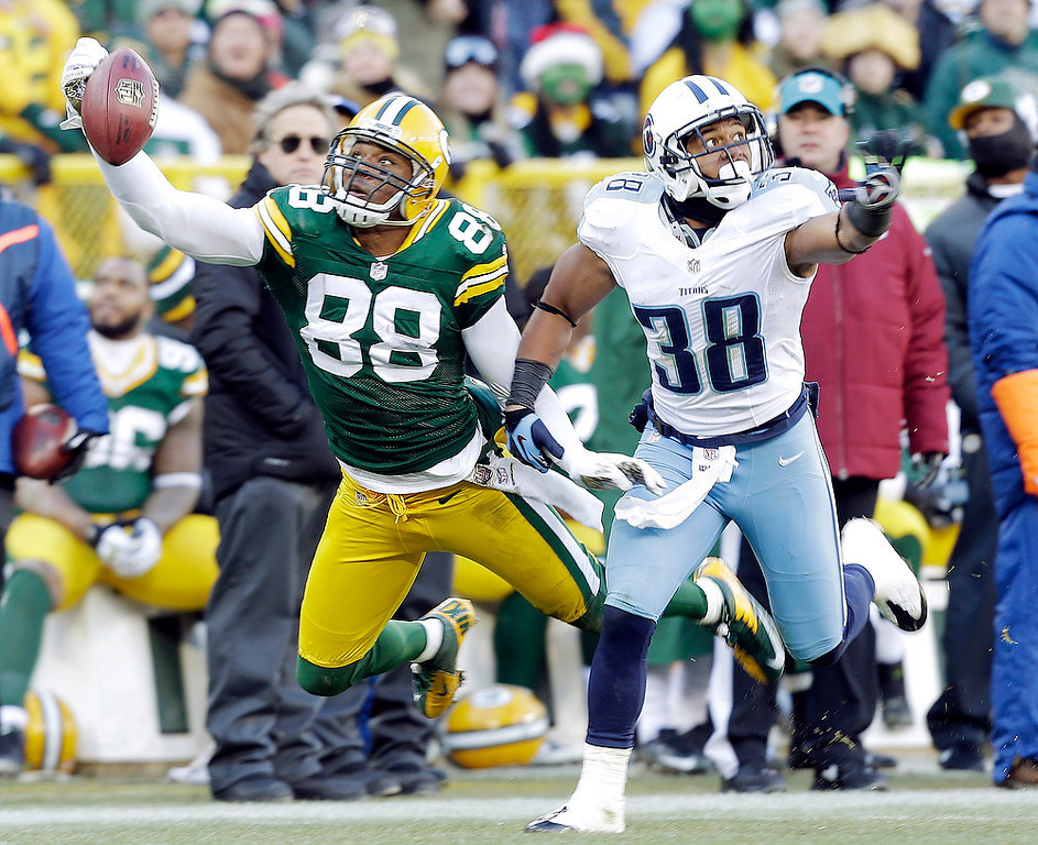 . Tennessee Titans\' Al Afalava (38) breaks up a pass intended for Green Bay Packers\' Jermichael Finley (88) during the first half of an NFL football game Sunday, Dec. 23, 2012, in Green Bay, Wis. (AP Photo/Jeffrey Phelps)