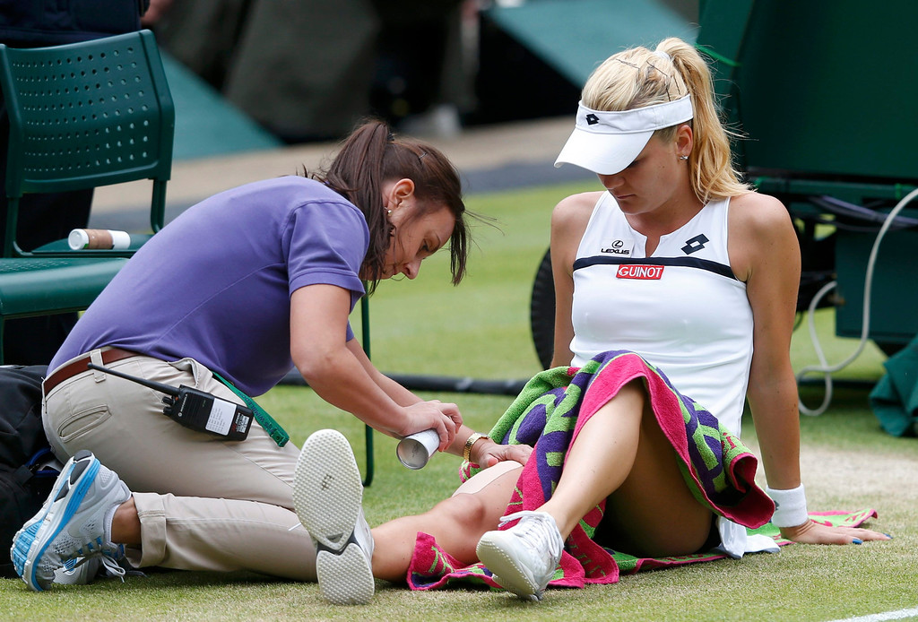 . Agnieszka Radwanska of Poland receives treatment in her women\'s quarter-final tennis match against Li Na of China at the Wimbledon Tennis Championships, in London July 2, 2013. REUTERS/Suzanne Plunkett