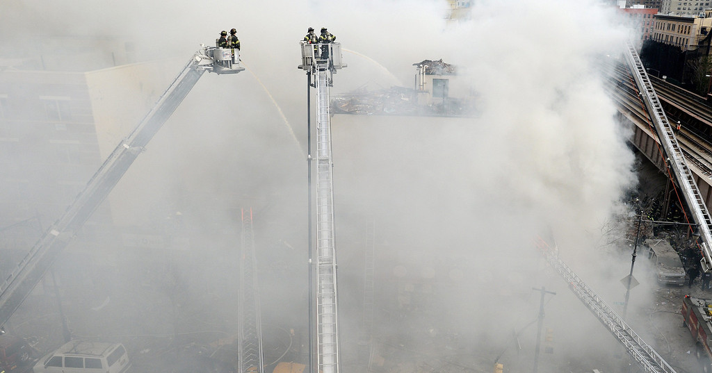 . Firefighters try to put out a fire after a reported explosion and building collapse in the Harlem area of New York City, New York, USA, 12 March 2014. The cause of the explosion, as well as reports of any injuries, had not yet been determined.  EPA/JUSTIN LANE