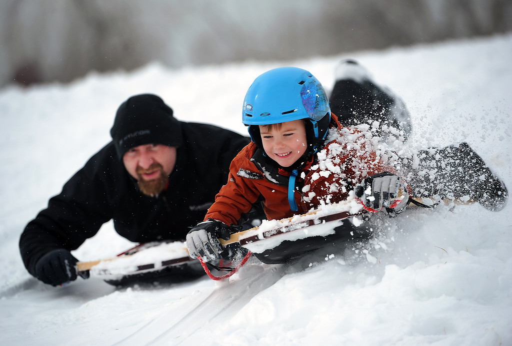 . Xander Smith, 5, of Boulder, tries to beat his father Steven down the hill as the two fly down the hill on Mountain Boy sleds which are similar to the old Radio Flyer sleds. Kids of all ages enjoyed sledding down a gently sloping hill in Scott Carpenter Park in Boulder on February 21, 2012.  Between 4-6 inches of freshly fallen snow created havoc on the metro area roadways but loads of fun for kids with a day off from school.   (Photo By Helen H. Richardson/ The Denver Post)