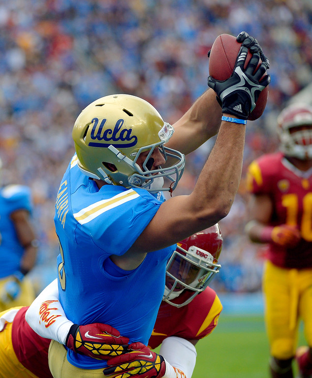 . UCLA tight end Joseph Fauria, top, scores a touchdown as  Southern California safety Jawanza Starling tries to make the stop during the first half of an NCAA college football game, Saturday, Nov. 17, 2012, in Pasadena, Calif. (AP Photo/Mark J. Terrill)