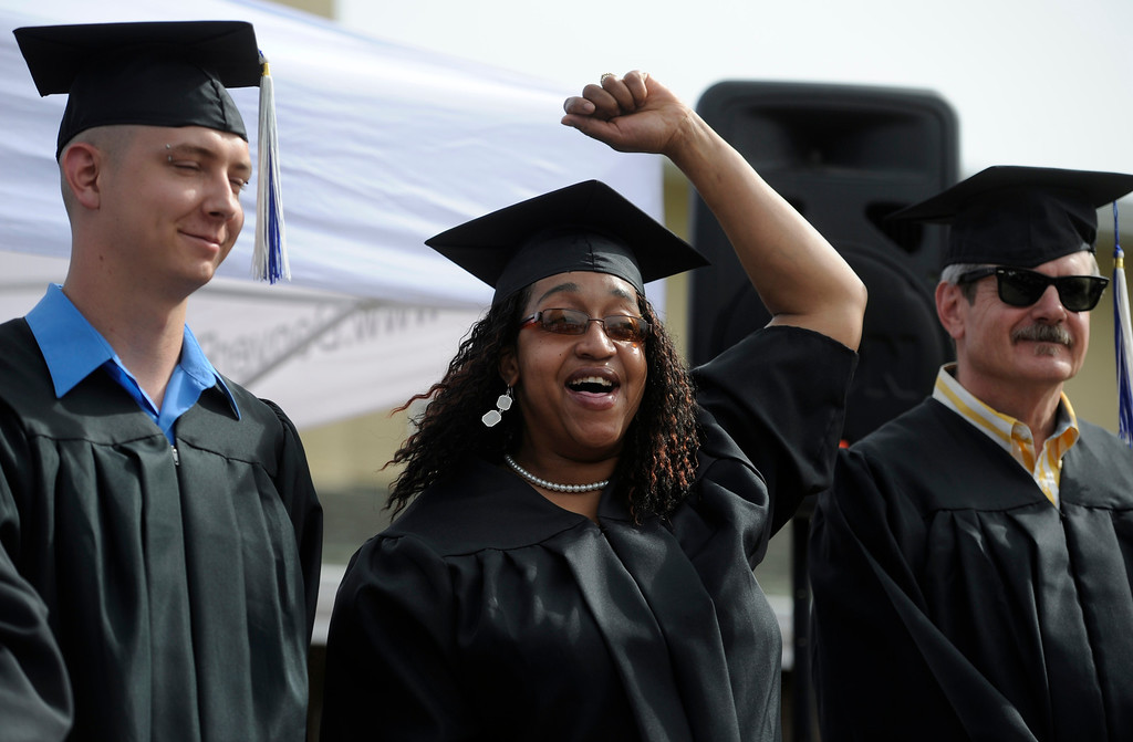 . Flanked by her fellow graduates Joshua Fuller, left, and Brad Barkey, right, Liberia Flowers raises her hand in a cheer after she receives her certificate. Participants in the Denver Rescue Mission\'s various programs celebrate a milestone with a graduation ceremony, including eleven men and women receiving their GED\'s. The ceremony, held at The Crossing transitional housing facility, celebrates and recognizes those who have overcome many obstacles including homelessness, addiction, personal and family tragedies, and unemployment. (Photo By Kathryn Scott Osler/The Denver Post)