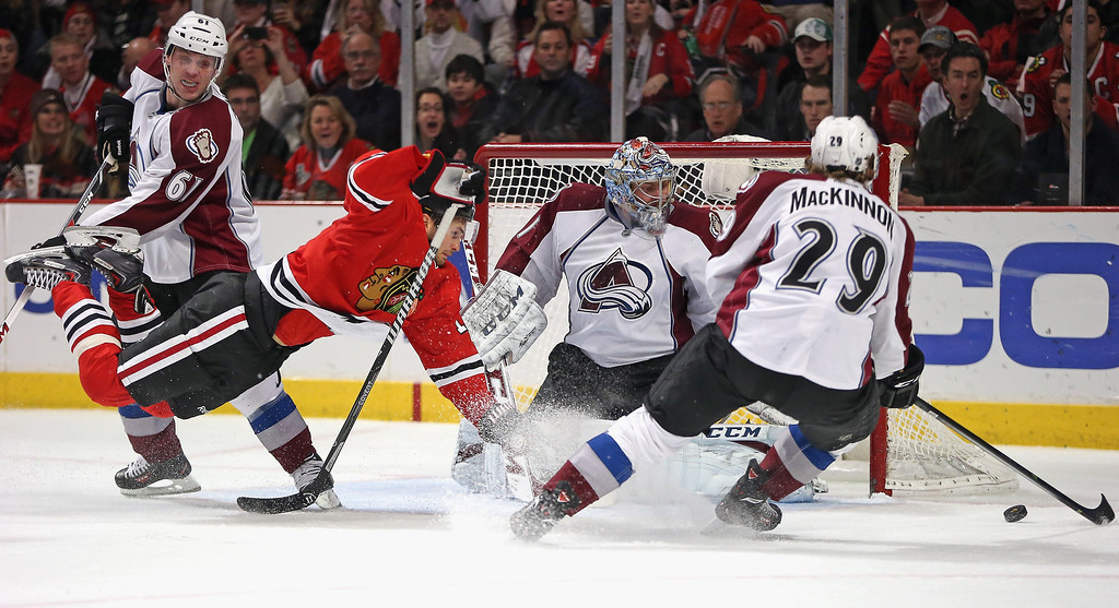 . Marcus Kruger #16 of the Chicago Blackhawks hits the ice chasing the puck against (L-R) Andre Benoit #61, Nathan MacKinnon #29 and Semyon Varlamov #1 of the Colorado Avalanche at the United Center on January 14, 2014  in Chicago, Illinois. (Photo by Jonathan Daniel/Getty Images)