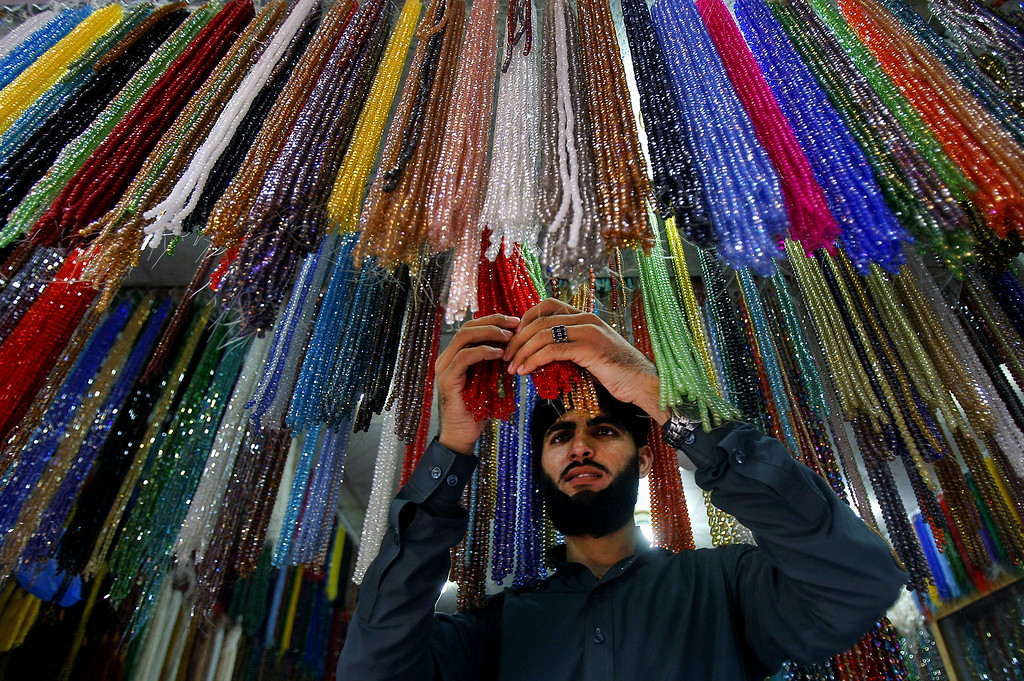 . A Pakistani vendor arranges praying beads which worshippers buy for Islamic holy month of Ramadan in Peshawar, Pakistan, Saturday, July 28, 2014. Muslims throughout the world are preparing to celebrate the holy fasting month of Ramadan, when they refrain from eating, drinking, and smoking from dawn to dusk. Muslims usually increase their religious activities during the Ramadan. (AP Photo/Mohammad Sajjad)
