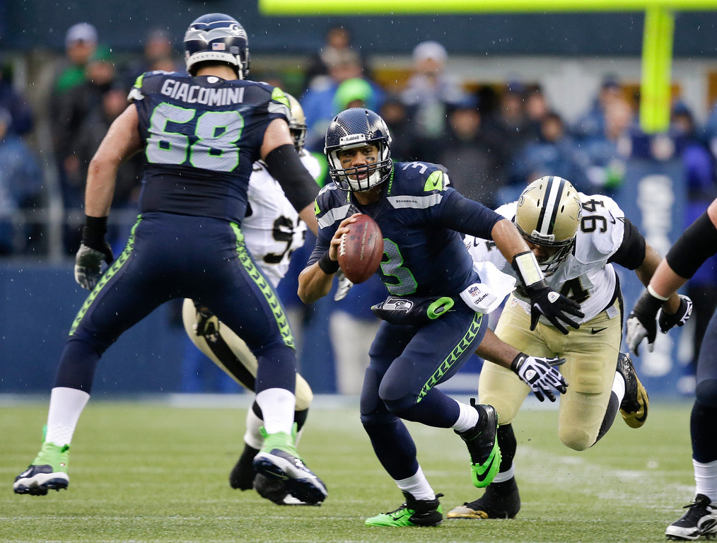 . Seattle Seahawks quarterback Russell Wilson (3) scrambles in front of New Orleans Saints defensive end Cameron Jordan (94) during the second quarter of an NFC divisional playoff NFL football game in Seattle, Saturday, Jan. 11, 2014. (AP Photo/Elaine Thompson)